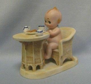 Neill Kewpie on platform with Wicker Chair & Table Having Breakfast