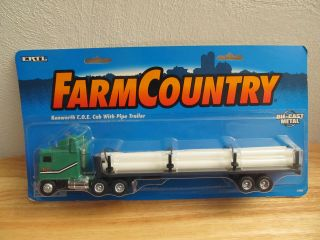 64th Kenworth Cabover semi truck with flatbed trailer and pipe load