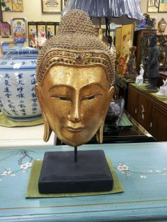 buddha head wood carving on stand with gold leaf thailand