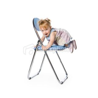 Cute 15 months girl climbing onto a blue chair Royalty Free Stock